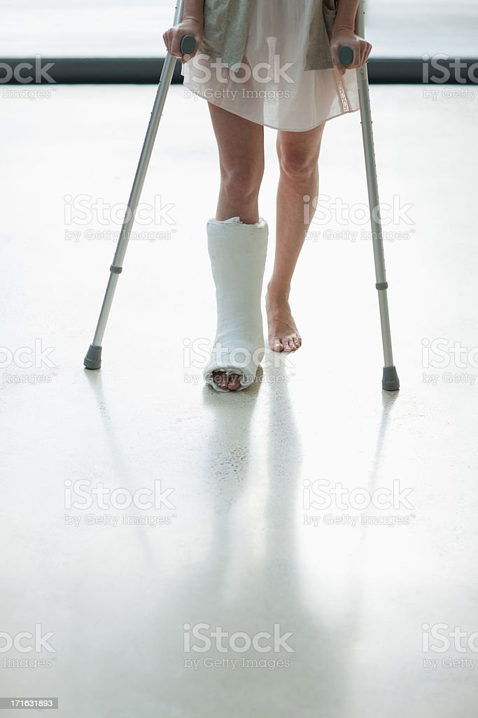 Person with cast on leg using crutches stock photo