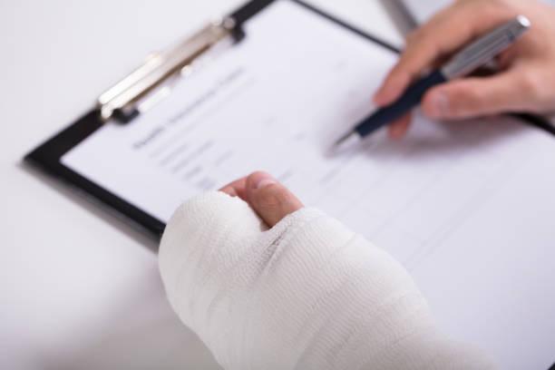 person with fractured hand filling health insurance form - soddisfazione foto e immagini stock