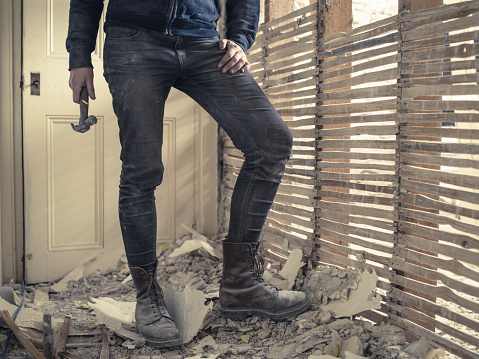 A person holding a hammer is standing by an old wattle and daub wall