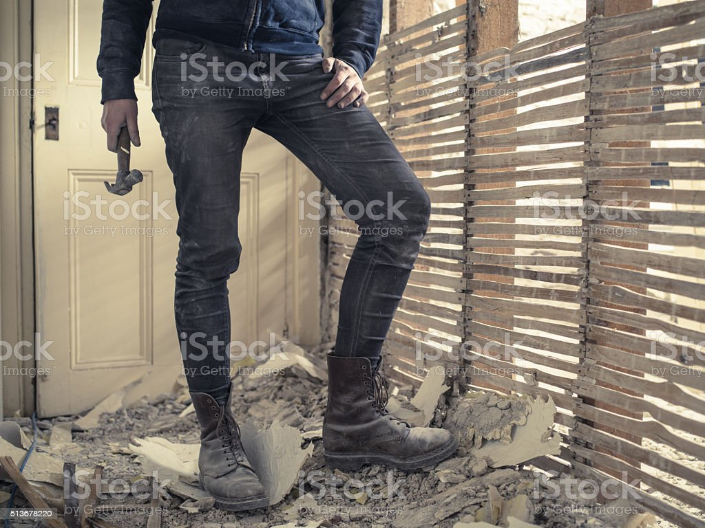 Person with hammer standing by wattle and daub wall stock photo