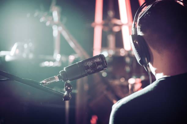 person mit kopfhörer und studio mikrofon close-up, in einer aufnahme studio oder konzertsaal mit einem drum-set. - medium strähnchen stock-fotos und bilder