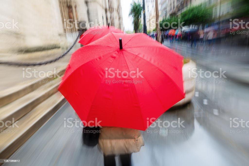 person with red umbrella in the rainy city with camera made zoom...