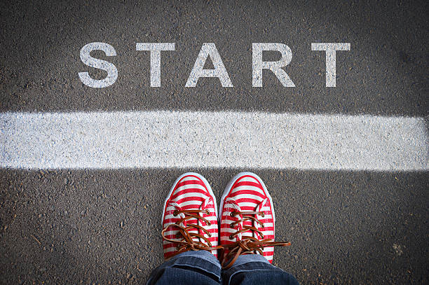 person with sneakers standing in front of the start message person with sneakers standing on the asphalt, in front of the start message single step stock pictures, royalty-free photos & images