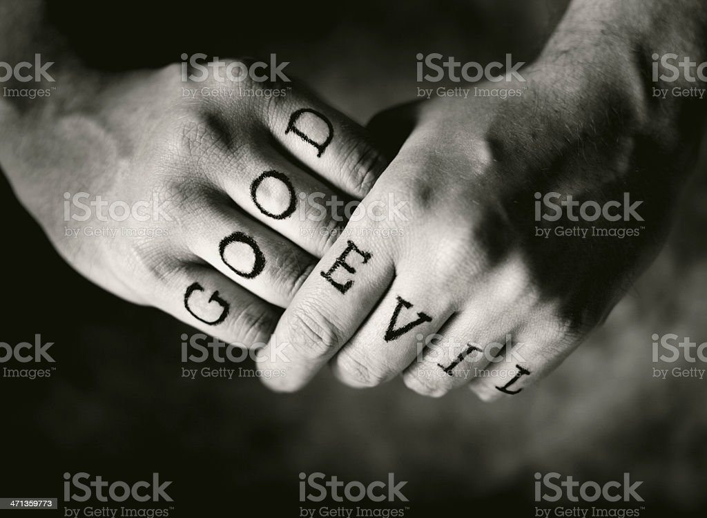 Person with the words good and evil written on their fingers stock photo