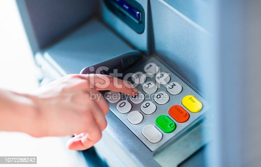 istock A person withdrawing money from a atm machine 1072288242