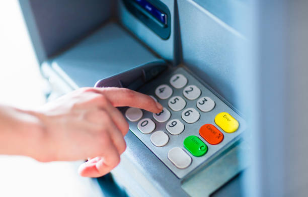 A person withdrawing money from a atm machine stock photo
