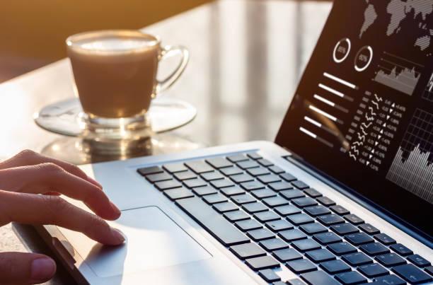 Person, die auf Einem Laptop-Computer mit Business Analytics- und Finanzberichtsdaten mit Metriken und Diagrammen auf dem Bildschirm am modernen Büroarbeitsplatz mit Sonnenuntergangslicht und Kaffee arbeitet – Foto
