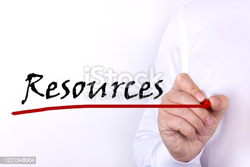 A person writes text, a word, the phrase Resources with marker on a light background. Business concept.