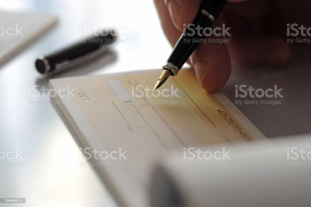 Person writing a check to pay off something, or giving away stock photo