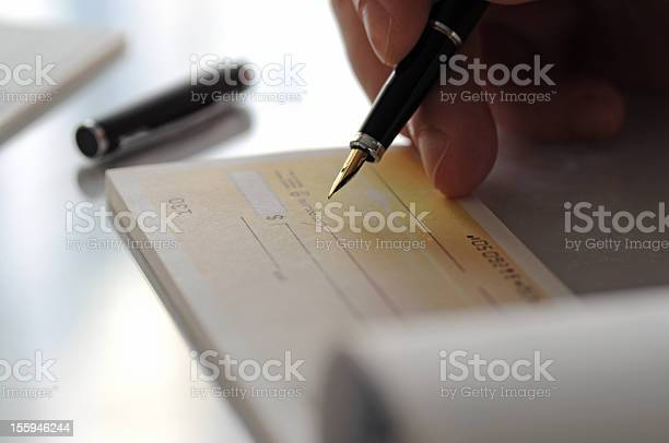 Person Writing A Check To Pay Off Something Or Giving Away Stock Photo - Download Image Now