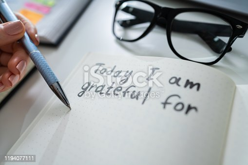 istock Person Writing I Am Grateful For Text 1194077111