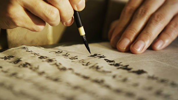 Person writing Japanese calligraphy in traditional style Close up of person carefully writing traditional Japanese calligraphy with a fudepen. calligraphy stock pictures, royalty-free photos & images