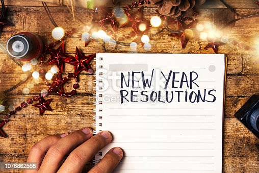 istock Person writing new year resolutions 1076862558