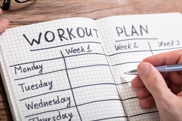 person schreiben trainingsplan in notebook - trainingstagebuch stock-fotos und bilder