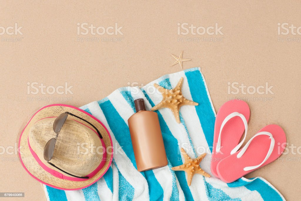 Personal accessories and sun protection cream on the sandy sea beach .