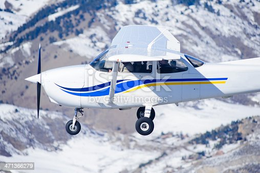 Small airplane (Cessna) flying with snow covered mountains behind, close up photo.