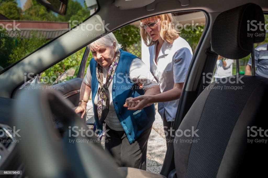 Persönlicher Assistent hilft, ältere Frau in Auto – Foto