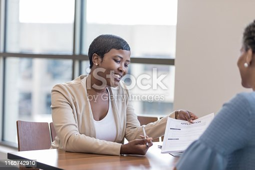 istock Personal banker explains account application to client 1165742910
