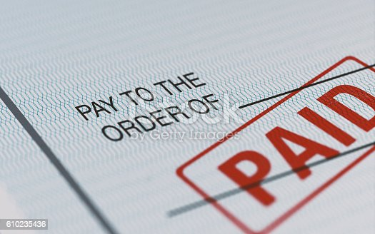 Close-up picture of a personal check with red paid stamp and selective focus. Great use for financial concepts.