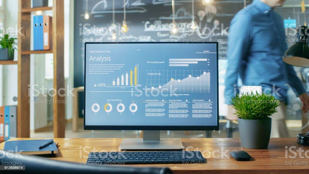 PC mit Mobile Anwendungsdesign zeigt auf dem Monitor steht auf den Schreibtisch, In den Hintergrund-Mann arbeitet tagsüber im Büro. – Foto