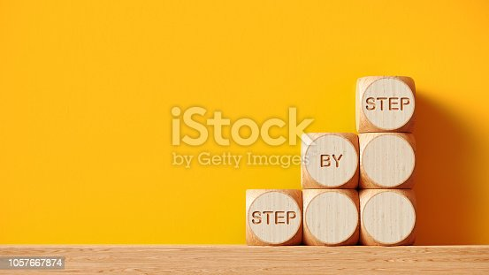 Wooden toy blocks in front of yellow wall background. Step by step writes on the wooden toy blocks. Horizontal composition with copy space.