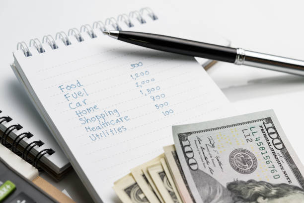 personal expense calculation or pay day concept, hand writing list numbers of expenses monthly cost on small paper white notepad with pen and us dollar bills on white table in soft tone - home finances stock pictures, royalty-free photos & images