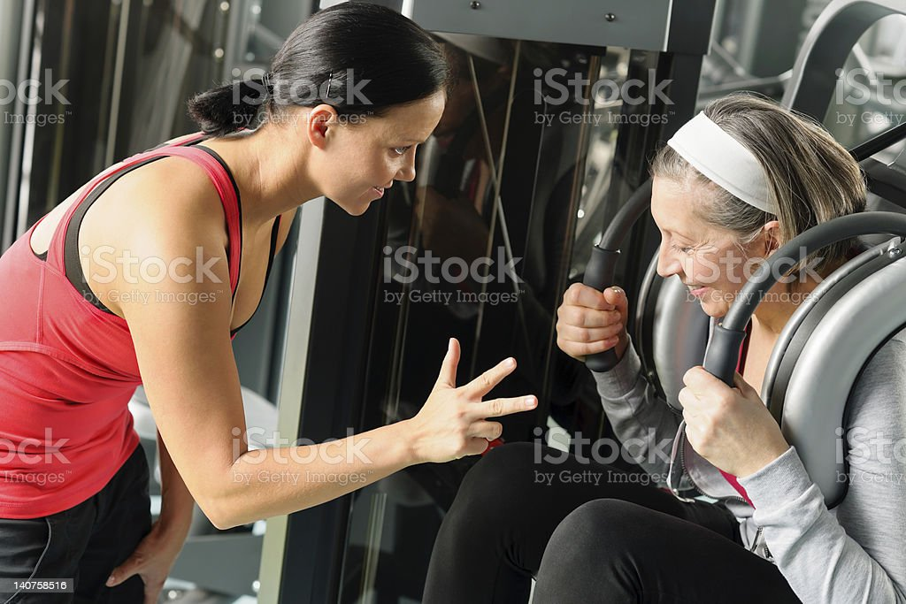 Personal fitness trainer with senior woman exercise royalty-free stock photo