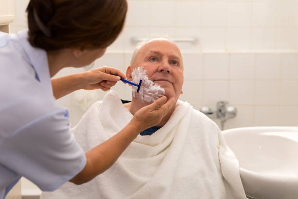 higiene personal-casa cuidador con hombre mayor en cuarto de baño - cuidado del cuerpo fotografías e imágenes de stock
