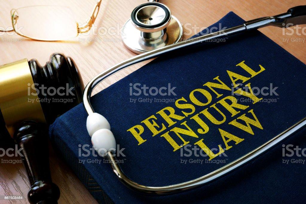 Concepto de ley de lesiones personal. Libro y un estetoscopio. - foto de stock