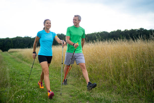 personal nordic walking instructor with female customer concentrated woman learning correct nordic walking technique from her personal trainer explaining during outdoor training on natural path between high grass on thundery summer afternoon nordic walking stock pictures, royalty-free photos & images