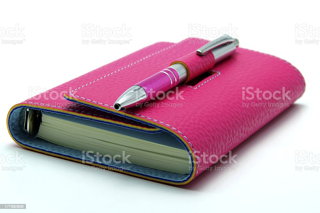 Personal Organizer in Pink Color with Ballpoint on White Background royalty-free stock photo