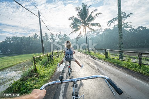 istock Personal perspective- couple cycling near rice fields at sunrise, Indonesia 925256070