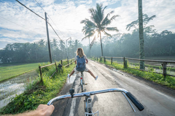 Personal perspective- couple cycling near rice fields at sunrise, Indonesia stock photo