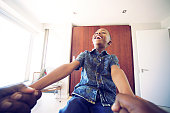 A Personal perspective having fun holding boy's hands while he is hanging on leaning back in the bedroom Strand Cape Town South Africa