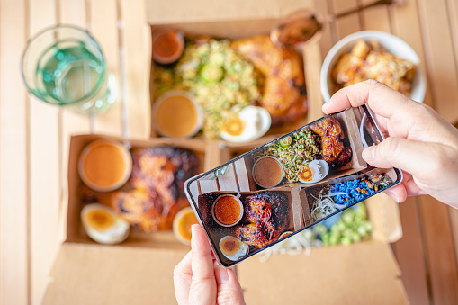Personal perspective human hand taking photo using smart phone on table top view malaysian food nasi kerabu, nasi ulam and ayam percik in recycled paper container with sauce