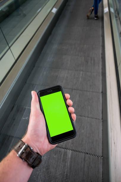 persoonlijk perspectief van een man te kijken naar zijn mobiele telefoon in de luchthaven. - foto's van business people on computer stockfoto's en -beelden