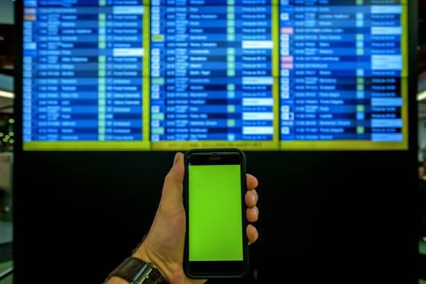 persoonlijk perspectief van een man te kijken naar zijn mobiele telefoon in een luchthaven. - foto's van business people on computer stockfoto's en -beelden