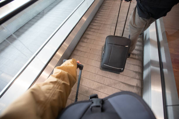 Personal Perspective of a Man Pulling Suitcase on Airport stock photo