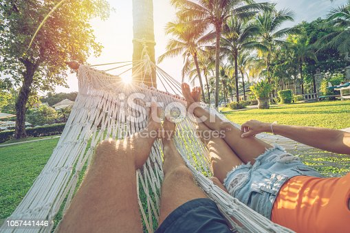 Personal perspective of couple relaxing on hammock, feet view. Couple's point of view from hammock  in tropical garden at sunset, barefoot. People travel tropical climate concept.