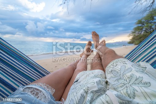 910783248 istock photo Personal perspective of couple relaxing on hammock, feet view 1148311930