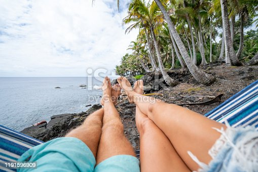 910783248 istock photo Personal perspective of couple relaxing on hammock, feet view 1191596909