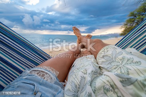 910783248 istock photo Personal perspective of couple relaxing on hammock, feet view 1192624016