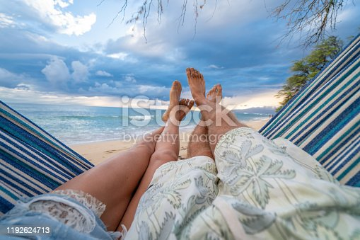 910783248 istock photo Personal perspective of couple relaxing on hammock, feet view 1192624713