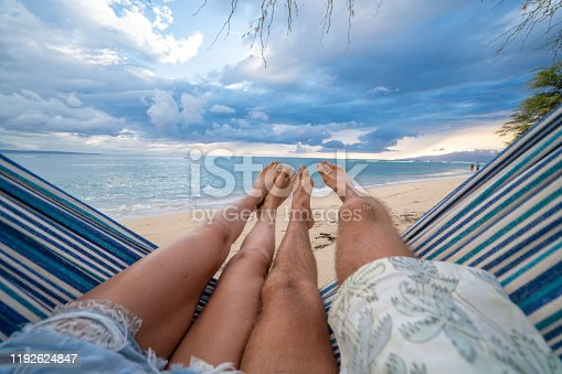 910783248 istock photo Personal perspective of couple relaxing on hammock, feet view 1192624847