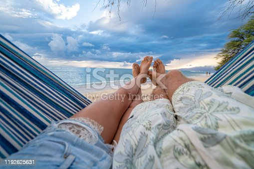 910783248 istock photo Personal perspective of couple relaxing on hammock, feet view 1192625631
