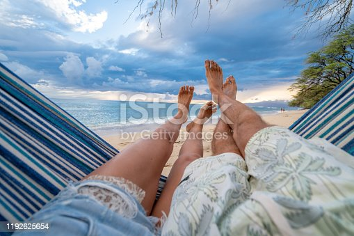 910783248 istock photo Personal perspective of couple relaxing on hammock, feet view 1192625654