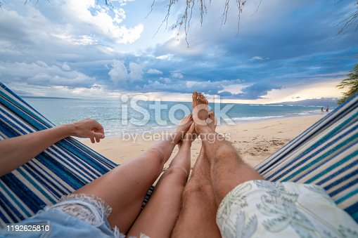 910783248 istock photo Personal perspective of couple relaxing on hammock, feet view 1192625810
