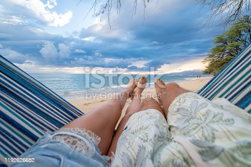 910783248 istock photo Personal perspective of couple relaxing on hammock, feet view 1192626652