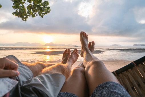 Couple's point of view from hammock on the beach at sunrise, barefoot.