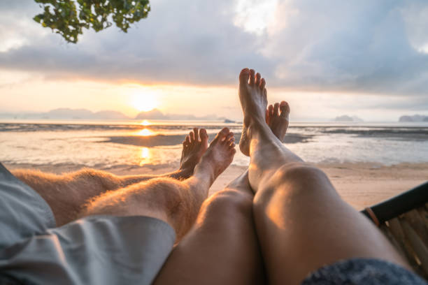 personal perspective of couple relaxing on hammock, feet view - woman leg beach pov stock photos and pictures